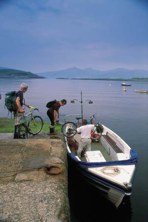 The ferryman helps two cyclists load their bikes on to the passenger ferry, the